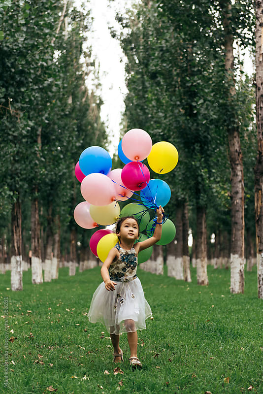Adorable little holding a bunch of balloon and running by MaaHoo Studio for Stocksy United