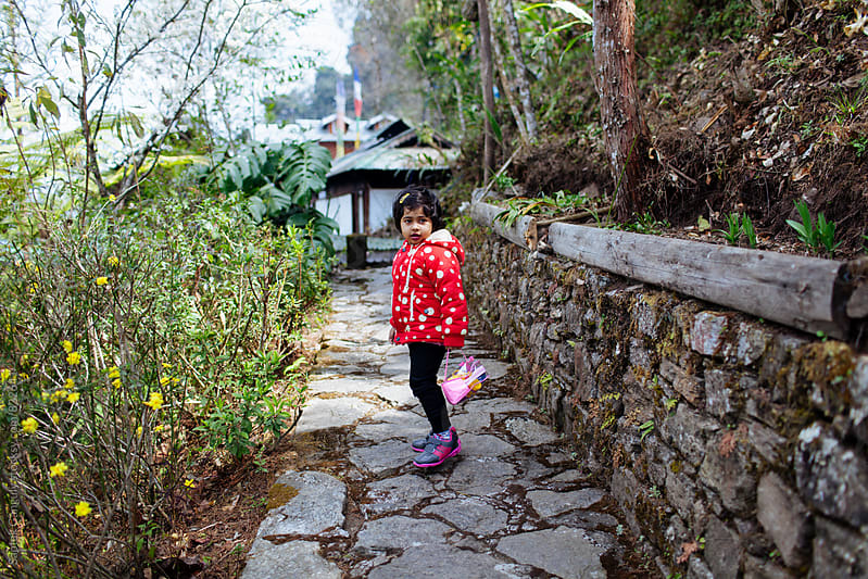 Child stands on a rock path and looking back by Saptak Ganguly for Stocksy United