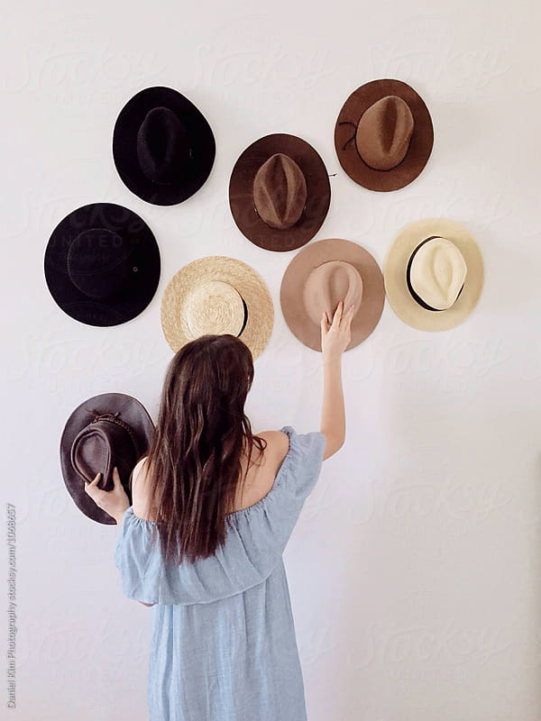 Woman placing hats on wall by Daniel Kim Photography for Stocksy United