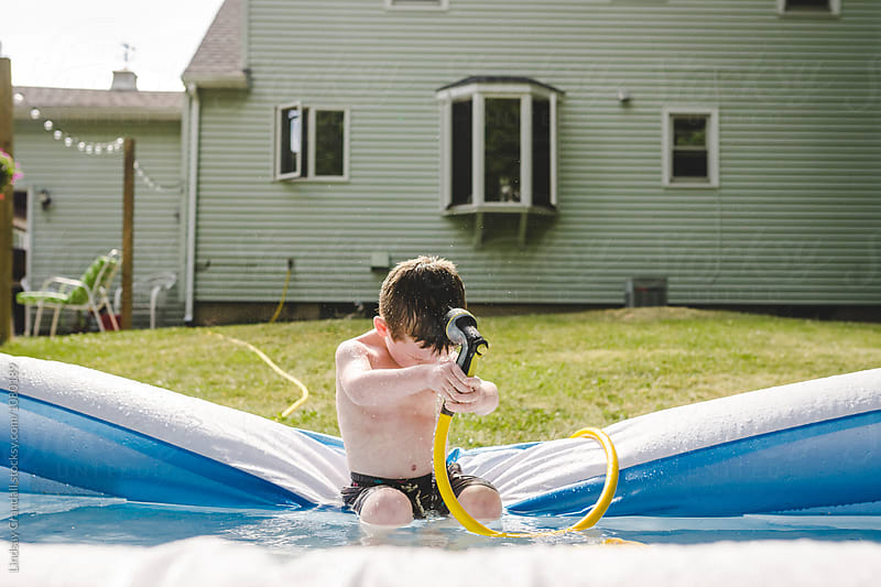 Young boy sitting on edge of kiddie pool spraying his head with water by Lindsay Crandall for Stocksy United
