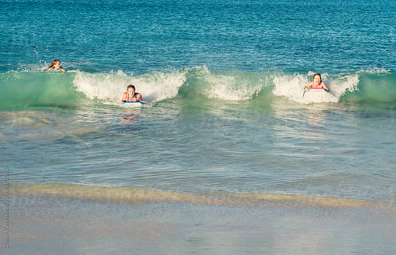 three girls bodysurfing at the beach by Gillian Vann for Stocksy United
