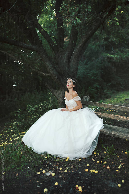 Beautiful bride in a romantic wedding dress sitting on a bench by Jovana Rikalo for Stocksy United