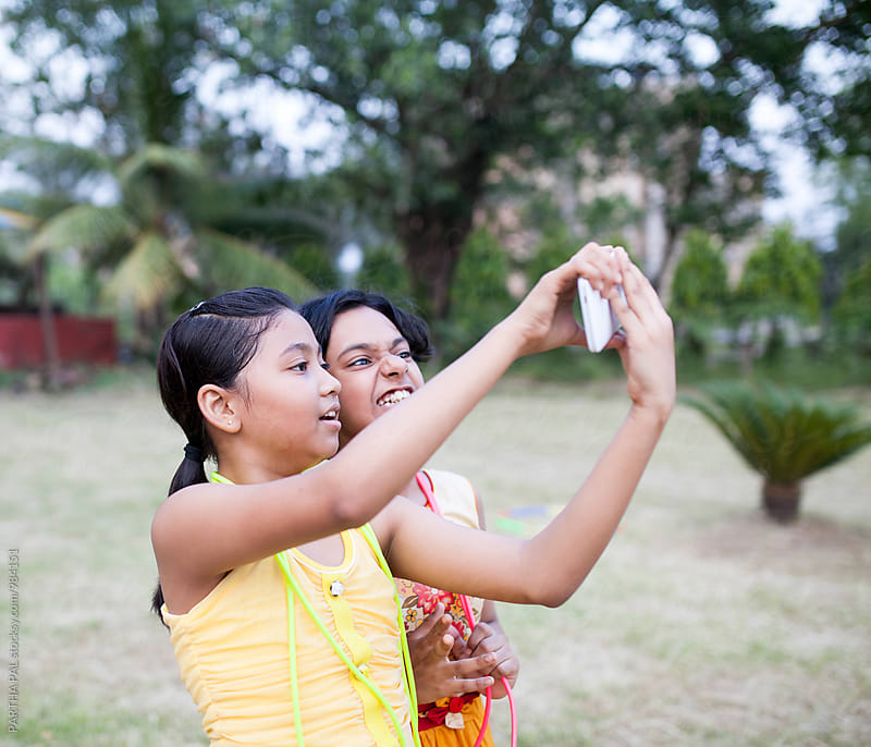 Two girls taking selfie in smartphone by PARTHA PAL for Stocksy United