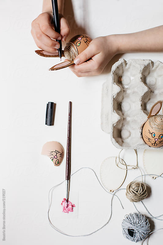 Hands drawing bunny face on en egg as Easter Diy project by Beatrix Boros for Stocksy United