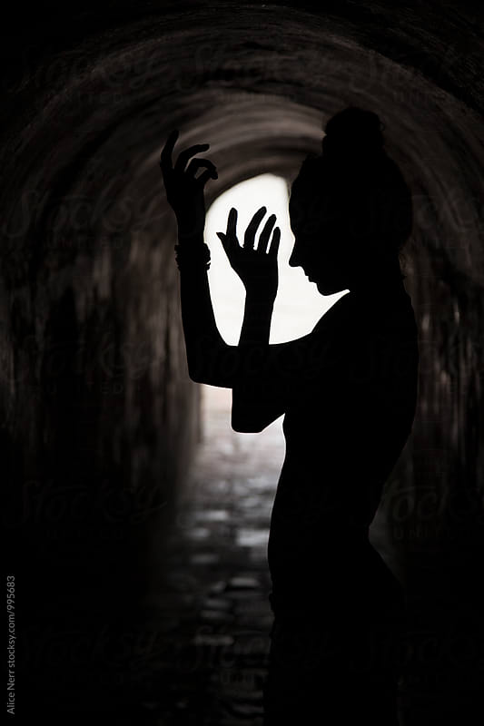 Female's silhouette in a dark tunnel by Alice Nerr for Stocksy United