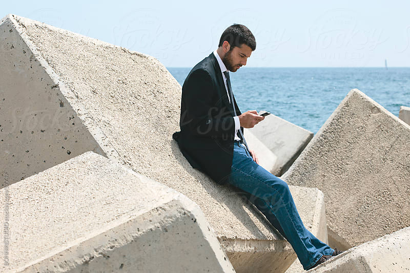 Businessman sending text message with phone on breakwater. by BONNINSTUDIO for Stocksy United