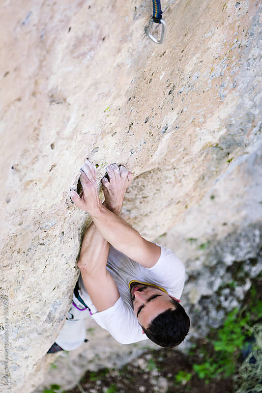 Man lead climbing vertical rout on a wall outdoors  by Jovana Milanko for Stocksy United