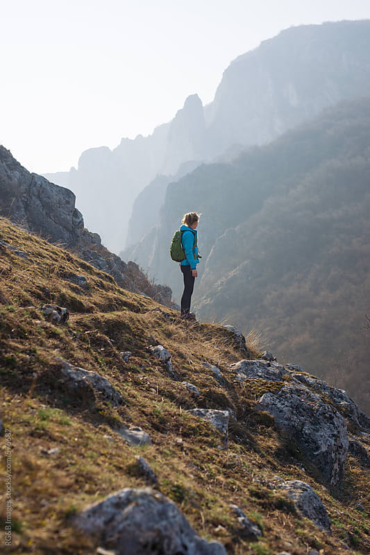 Female backpacker standing in the morning sunlight in a mountain landscape by RG&B Images for Stocksy United