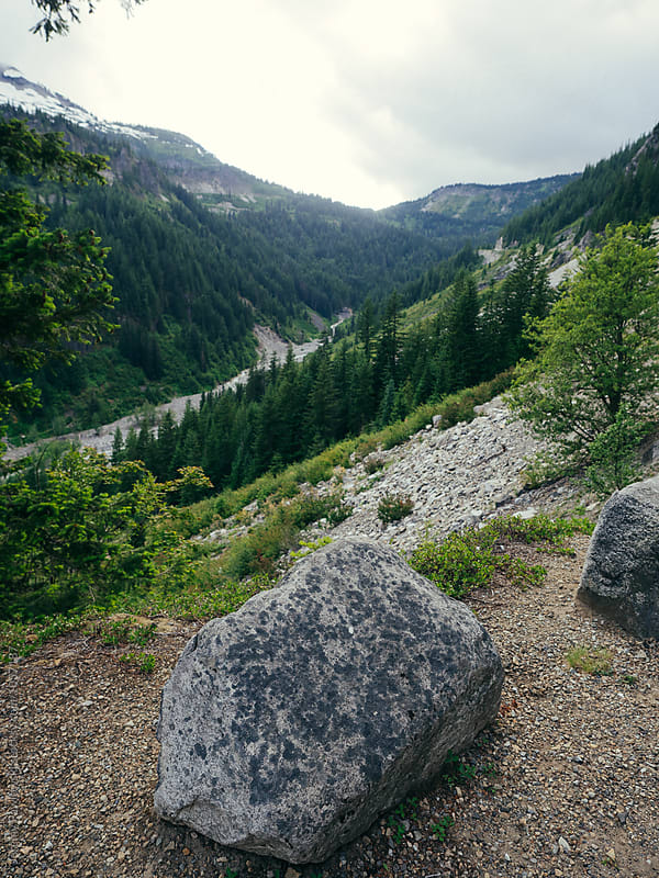 Rock in foreground with mountains, river and valley in background by Jeremy Pawlowski for Stocksy United