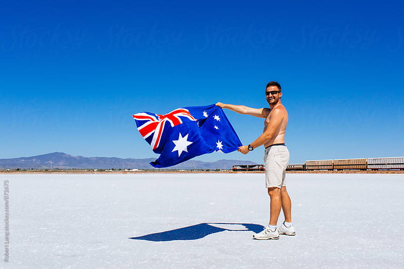 Man holds up the flag of Australia for Australia Day by Robert Lang for Stocksy United