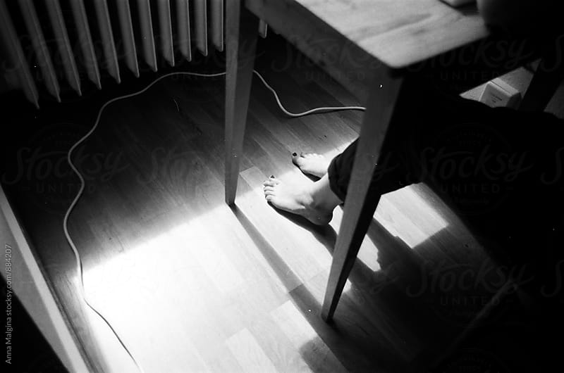 a film photo of foot standing on the light under the table by Anna Malgina for Stocksy United