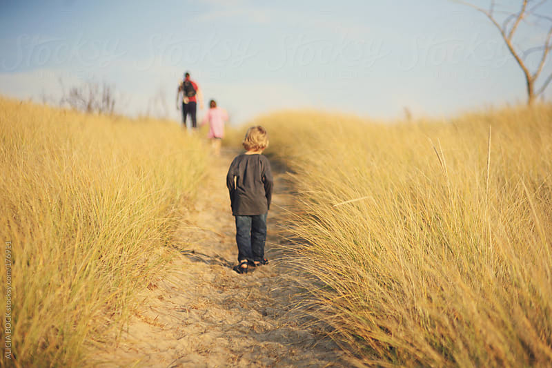 Family Walking Up A Sand Dune by ALICIA BOCK for Stocksy United