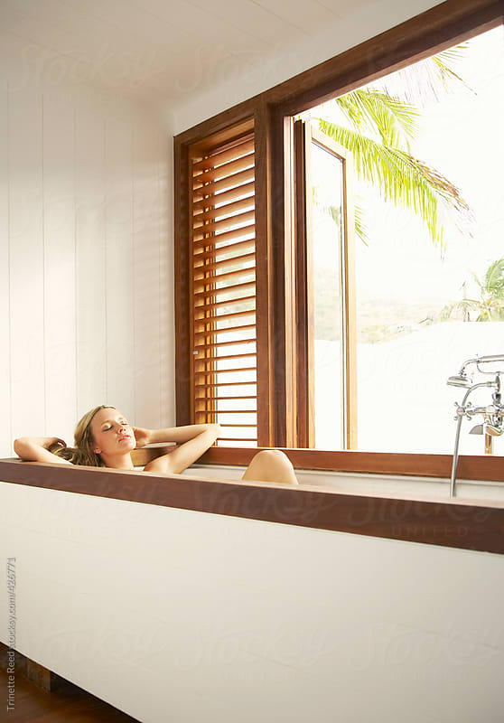 Woman relaxing in bathtub at luxury resort by Trinette Reed for Stocksy United