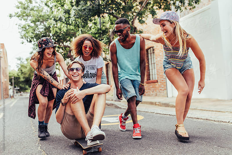 Group of multiracial young people enjoying themselves on the city street by Jacob Lund for Stocksy United