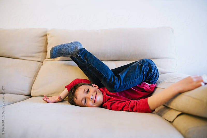 Little boy having fun on the sofa. by BONNINSTUDIO for Stocksy United