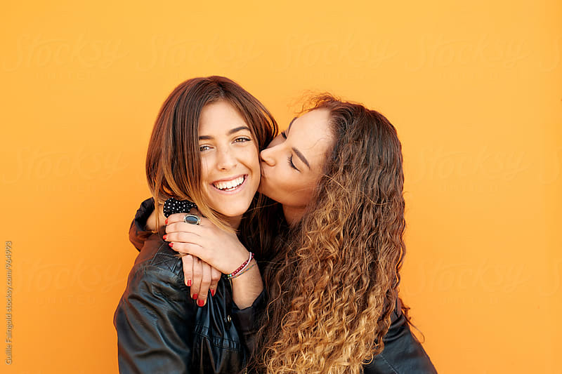 Happy friend smiling at camera while curly-haired girl kissing her by Guille Faingold for Stocksy United