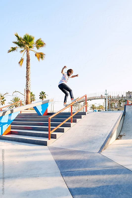 Young professional skater doing trick on railing by Guille Faingold for Stocksy United