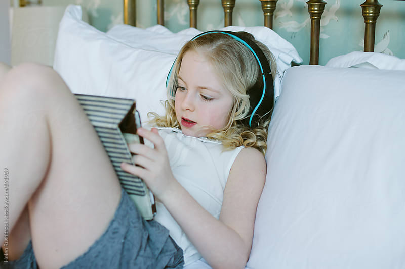 A little girl listening to music by Helen Rushbrook for Stocksy United