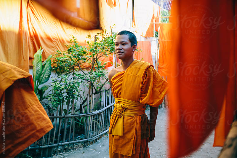 Young Buddhist monk walking out of the temple by michela ravasio for Stocksy United