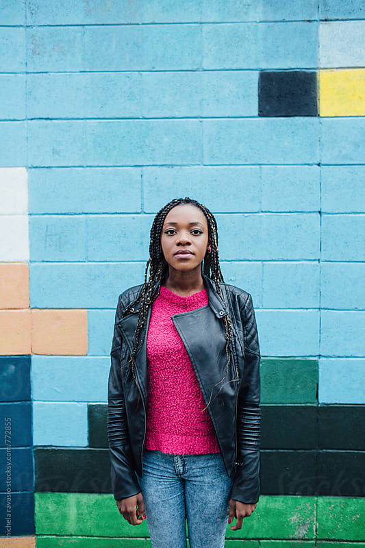Portrait of young African woman against a colorful wall by michela ravasio for Stocksy United