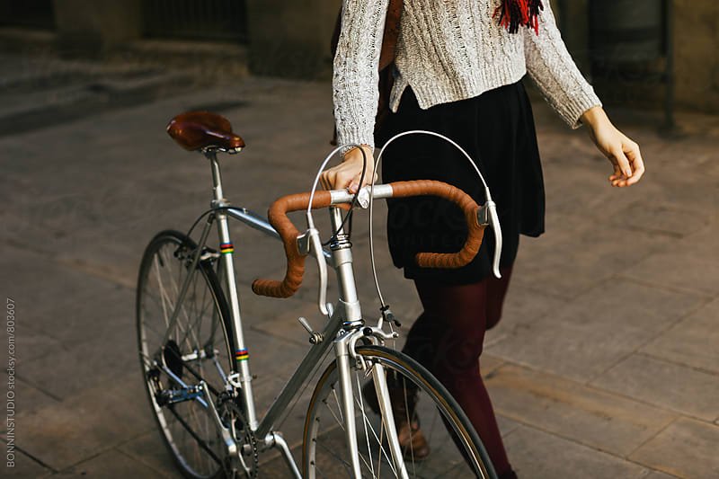 Closeup of a woman walking with her vintage bicycle on the street. by BONNINSTUDIO for Stocksy United