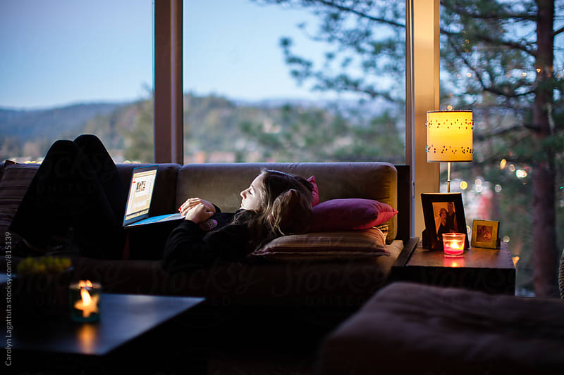 Teenage girl on the couch looking at her laptop by Carolyn Lagattuta for Stocksy United