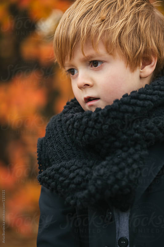 A portrait of a young boy in a big scarf looking away  by Ania Boniecka for Stocksy United