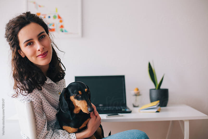Brunette woman posing with her small black dog by Marija Mandic for Stocksy United