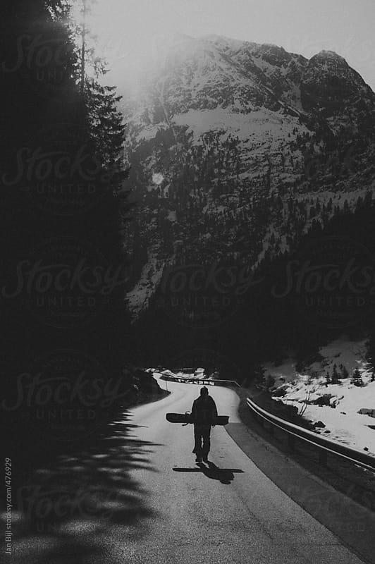 snowboarder walking up hill  to the skiresort by Jan Bijl for Stocksy United