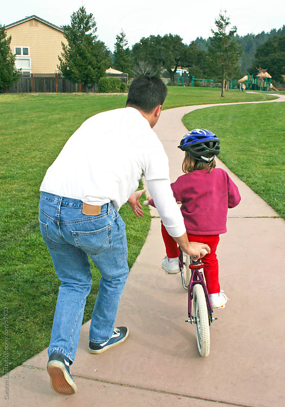 Father teaching his daughter to ride a bike for the first time by Carolyn Lagattuta for Stocksy United