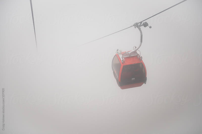 Cable car going up a misty mountain by Craig Holmes for Stocksy United