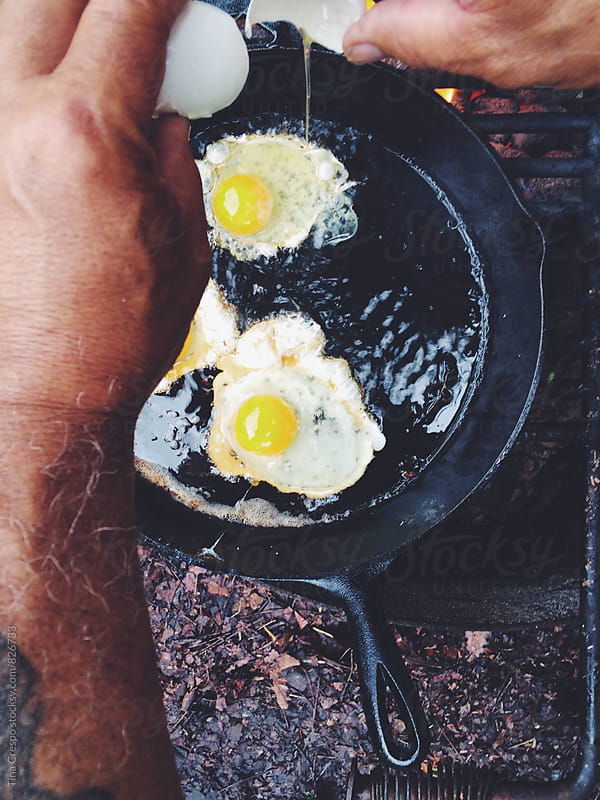 Cracking Eggs Over Skillet by Tina Crespo for Stocksy United