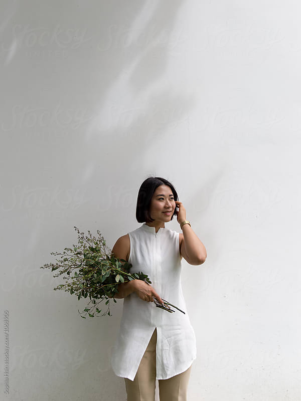 Girl in white shirt holding flowers by Sophia Hsin for Stocksy United