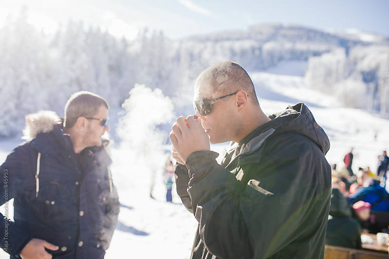 Two male friends drinking tea in the mountains by Maja Topcagic for Stocksy United