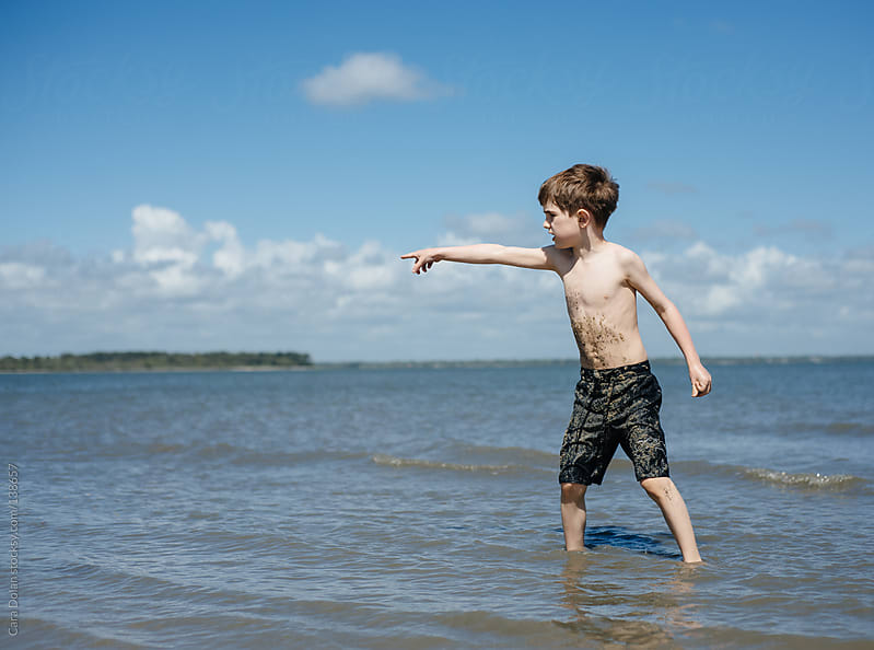 Boy wading in the ocean points at something he sees in the distance by Cara Dolan for Stocksy United
