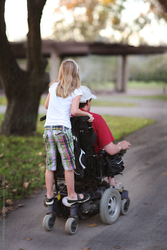 Child riding on back of wheelchair with disabled man by Dina Giangregorio for Stocksy United