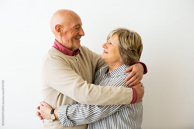 Portrait of an elderly couple embracing together at home.  by BONNINSTUDIO for Stocksy United