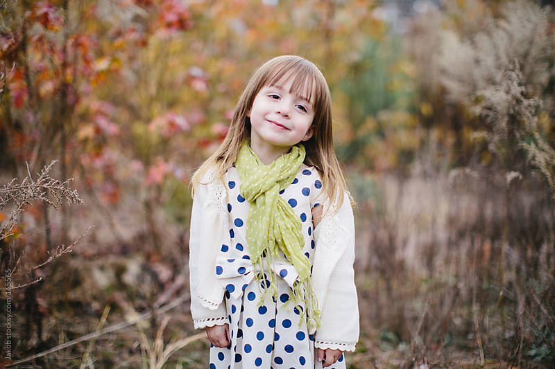 Portrait of a cute young child in a dress and scarf by Jakob for Stocksy United