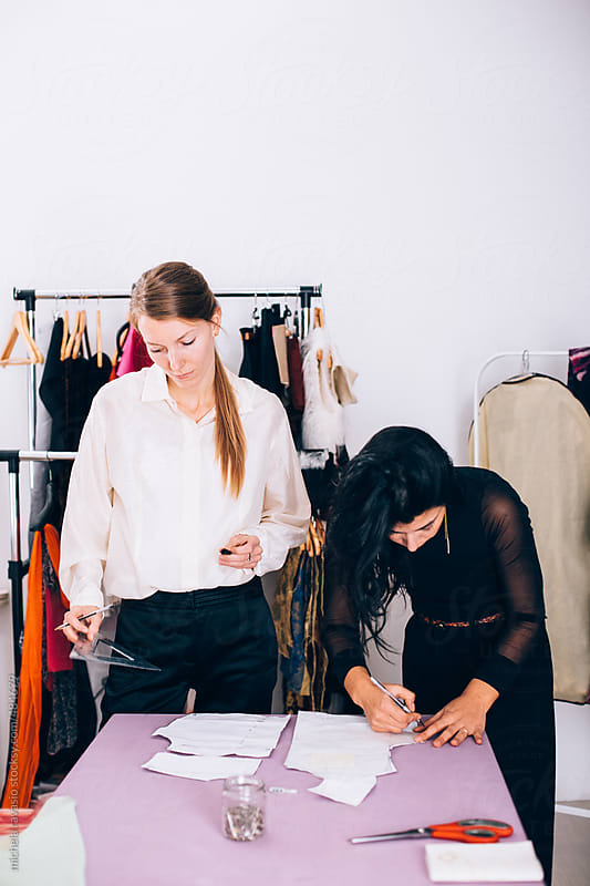 Two fashion designers  working on a paper pattern by michela ravasio for Stocksy United