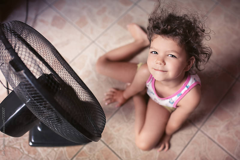 Young girl sitting in front of a fan letting her hair be blown. Shot from above. by Lea Csontos for Stocksy United