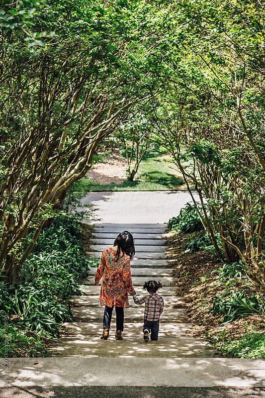 Mother and toddler girl, walking through a tunnel of trees by yuko hirao for Stocksy United