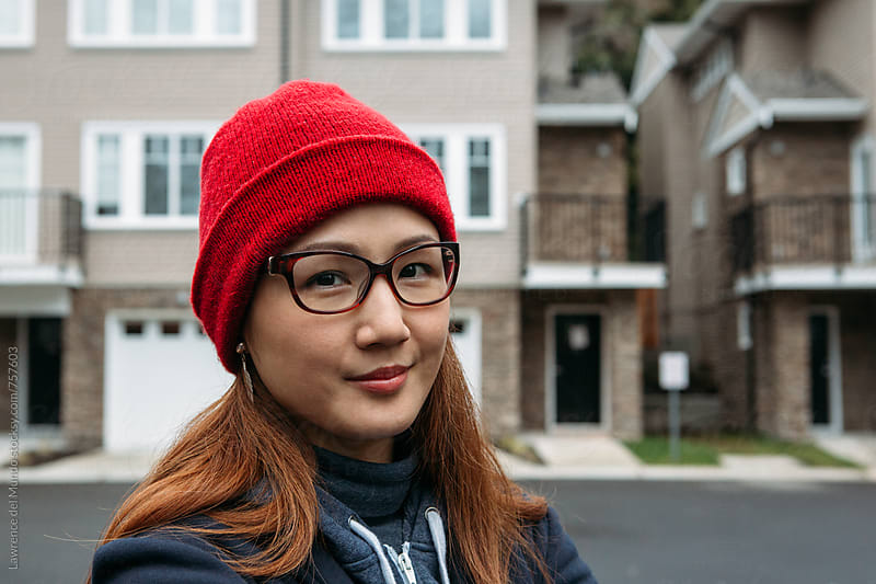 Portrait of a beautiful woman wearing cold weather clothes with new houses in the background by Lawrence del Mundo for Stocksy United