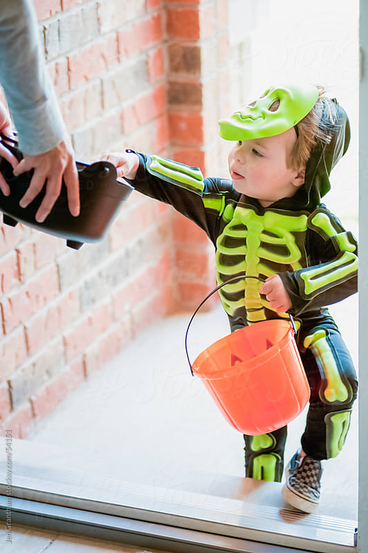 Toddler trick-or-treating in skeleton costume by Jen Grantham for Stocksy United