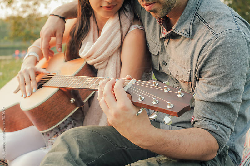 Couple playing guitar together in a park by Jovo Jovanovic for Stocksy United