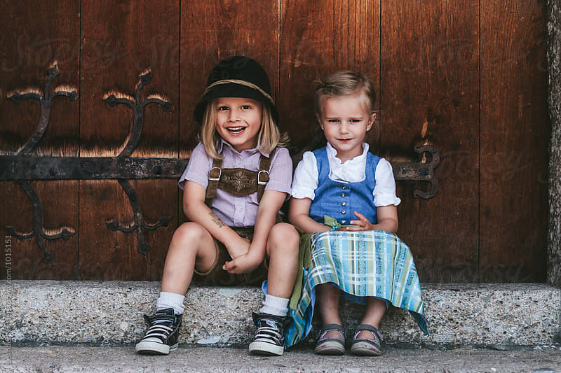 cute smiling children couple in dirndl dress and lederhosen  in front of wooden door by Leander Nardin for Stocksy United
