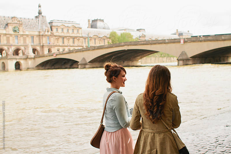 Two young women walk around Paris France by Jesse Morrow for Stocksy United
