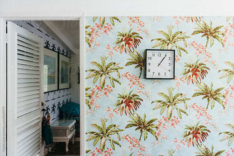 Room interior with vintage island wallpaper and clock by Trent Lanz for Stocksy United