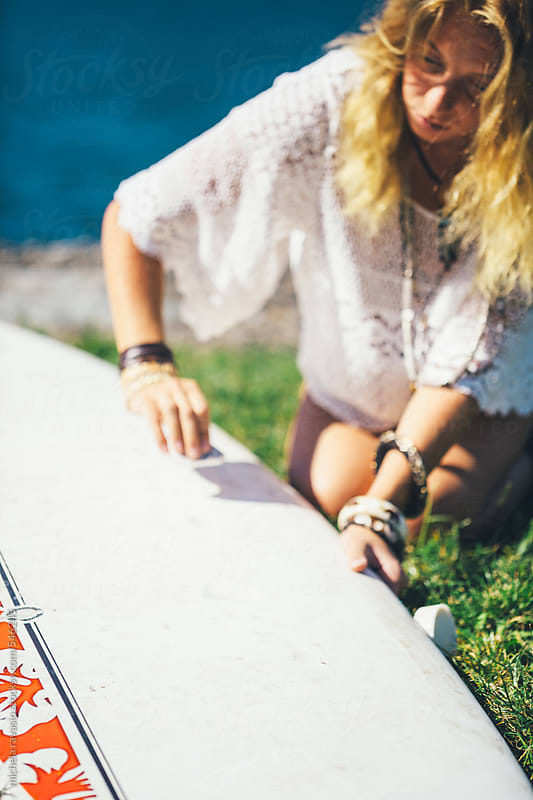 Woman waxing her surfboard  by michela ravasio for Stocksy United