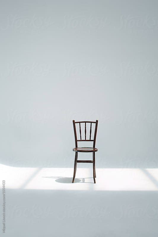 Old wooden chair in a white studio by Miquel Llonch for Stocksy United