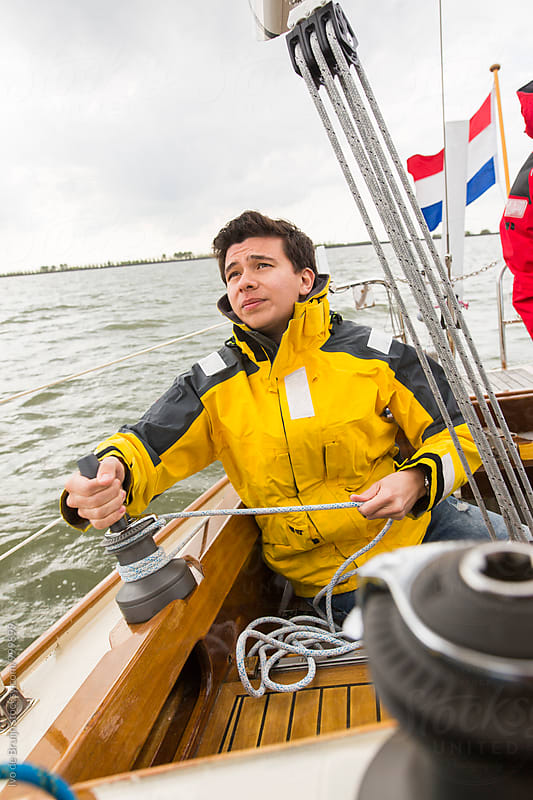 Young man steering a wooden sailboat, wearing a yellow sailing jacket. by Ivo de Bruijn for Stocksy United
